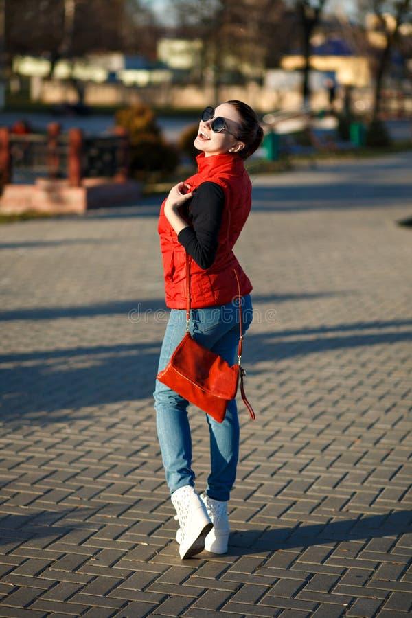A menina à moda ensolarada que ri alegremente, óculos de sol vestindo, vestiu-se em uma veste vermelha, equipamento da sarja de N imagem de stock royalty free