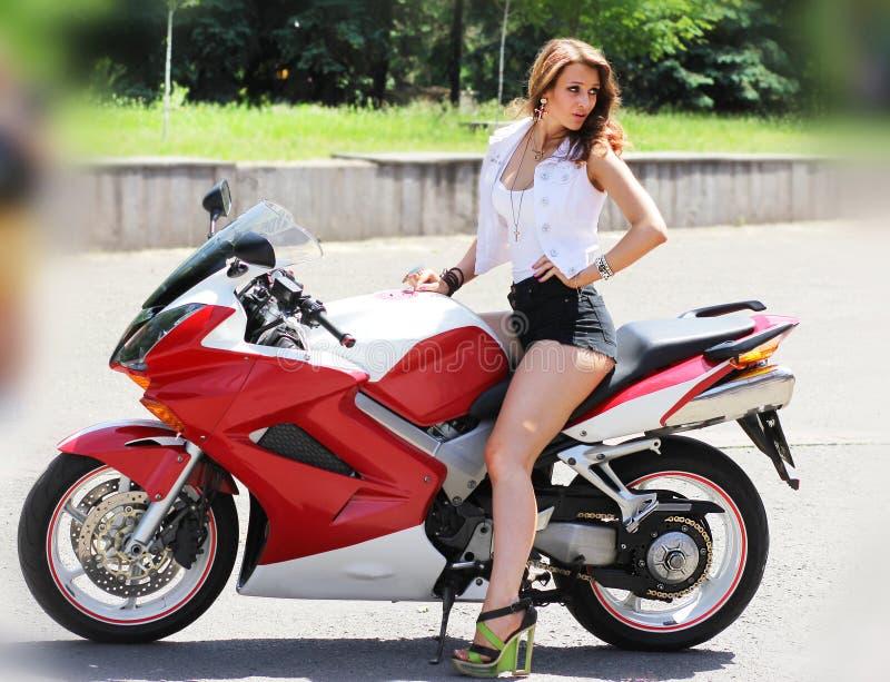 Menina à moda na motocicleta vermelha moderna imagens de stock