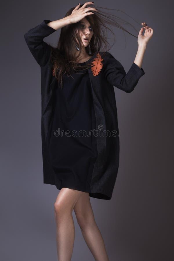 Menina à moda na roupa elegante de um outono e composição brilhante com o vento em seu cabelo fotografia de stock