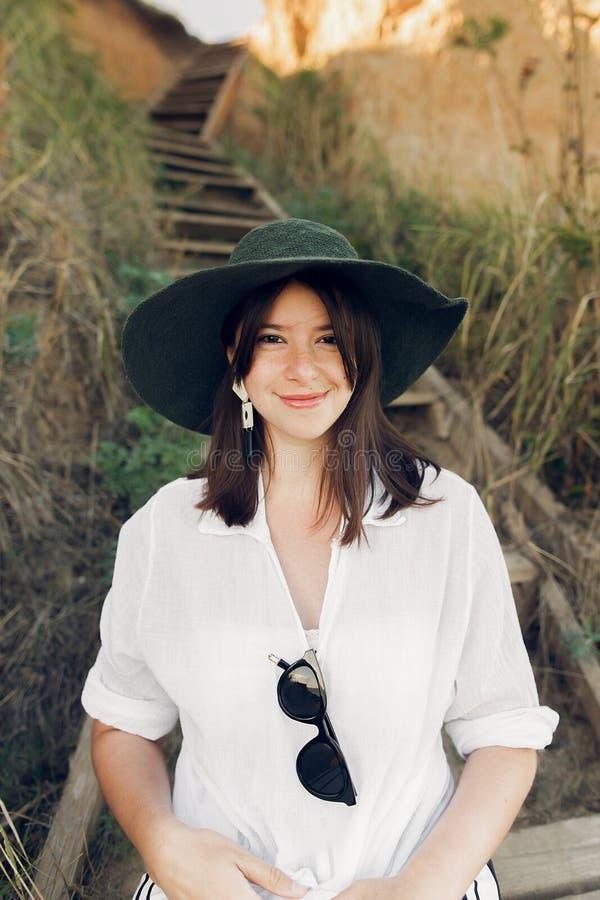 Menina à moda no olhar elegante que senta-se em escadas de madeira no penhasco da praia no mar na luz ensolarada Mulher nova feli imagem de stock