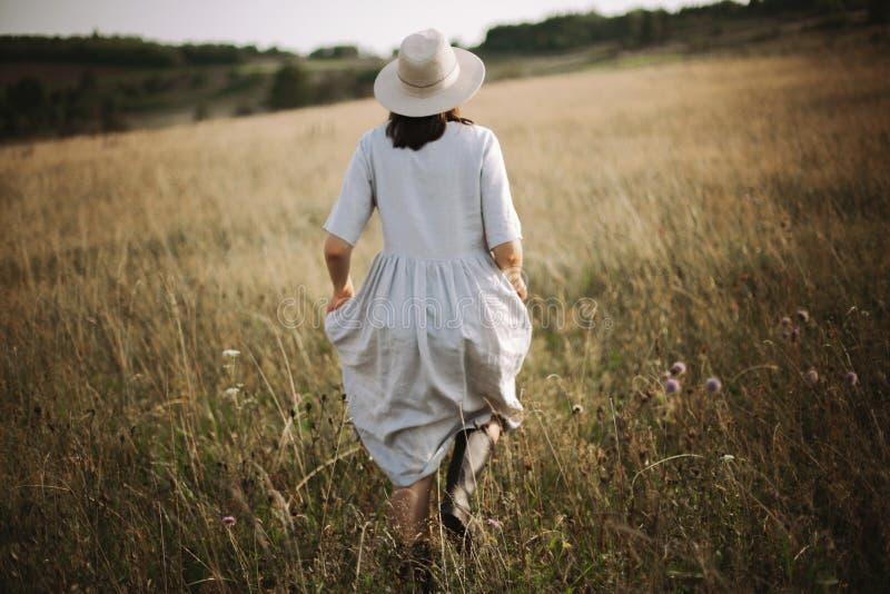 Menina à moda no vestido de linho que corre entre ervas e wildflowers no prado ensolarado nas montanhas Mulher de Boho que relaxa foto de stock