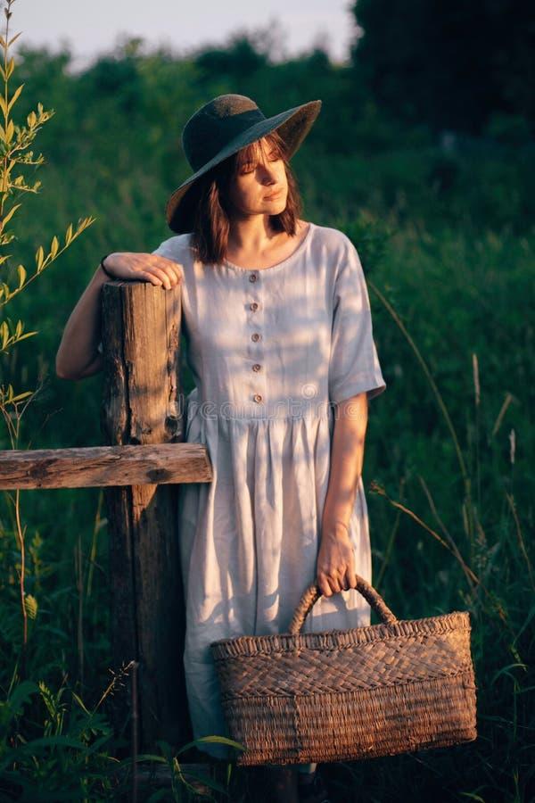 Menina à moda no vestido de linho que guarda a cesta rústica da palha na cerca de madeira na luz do por do sol Mulher de Boho que imagem de stock