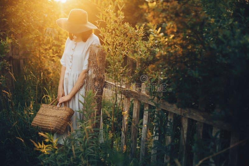 Menina à moda no vestido de linho que guarda a cesta rústica da palha na cerca de madeira na luz do por do sol Mulher de Boho que foto de stock royalty free