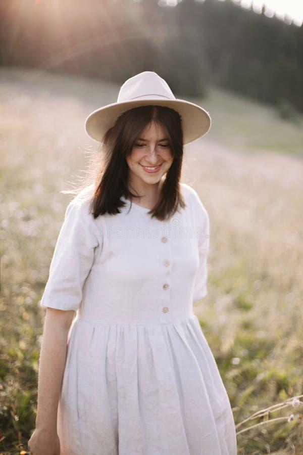 Menina à moda no vestido rústico que sorri e que anda nos wildflowers no prado ensolarado nas montanhas Retrato da mulher feliz d imagens de stock