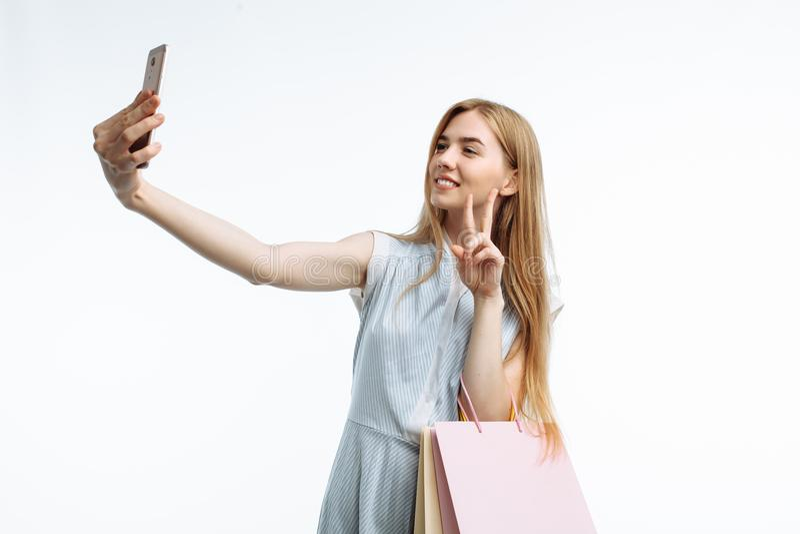 Menina à moda nova, com os sacos do presente, levantando e tomando um selfie o fotografia de stock royalty free