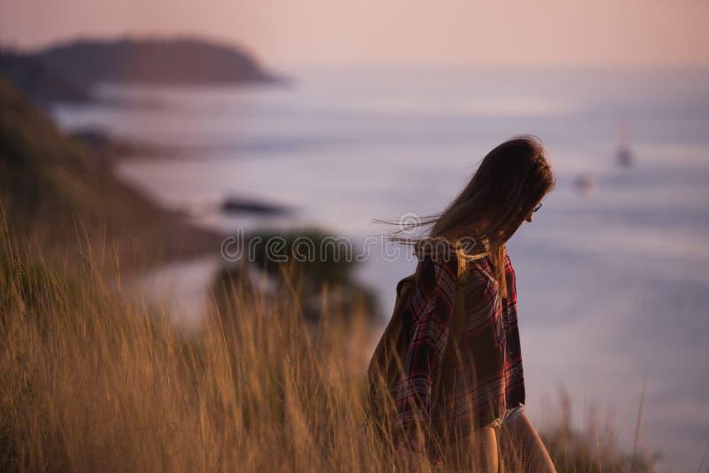 A menina à moda nova do moderno aprecia o por do sol no ponto de vista Mulher do curso com trouxa foto de stock