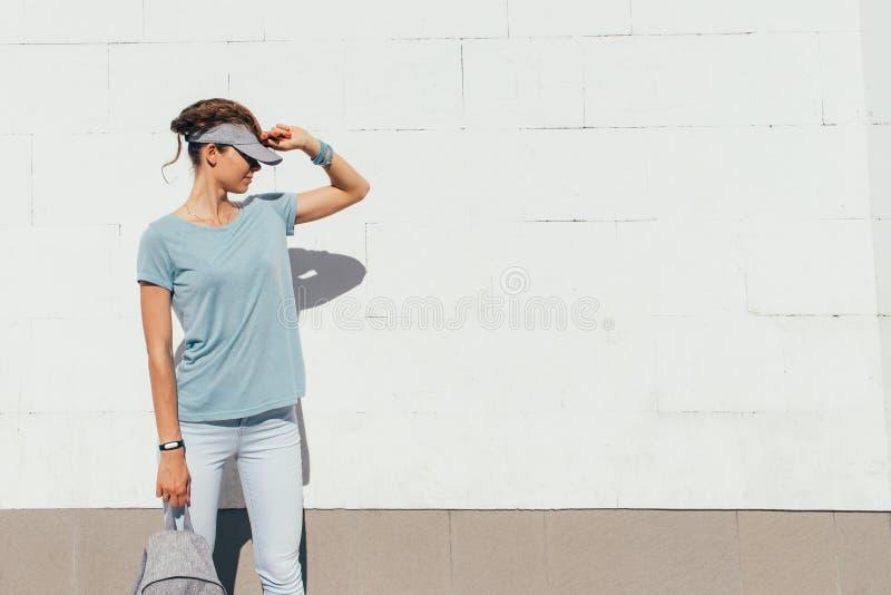 Menina à moda nova em um tampão em um fundo branco da parede foto de stock