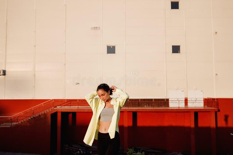 A menina à moda nova levanta na rua na frente da construção urbana no dia morno imagens de stock