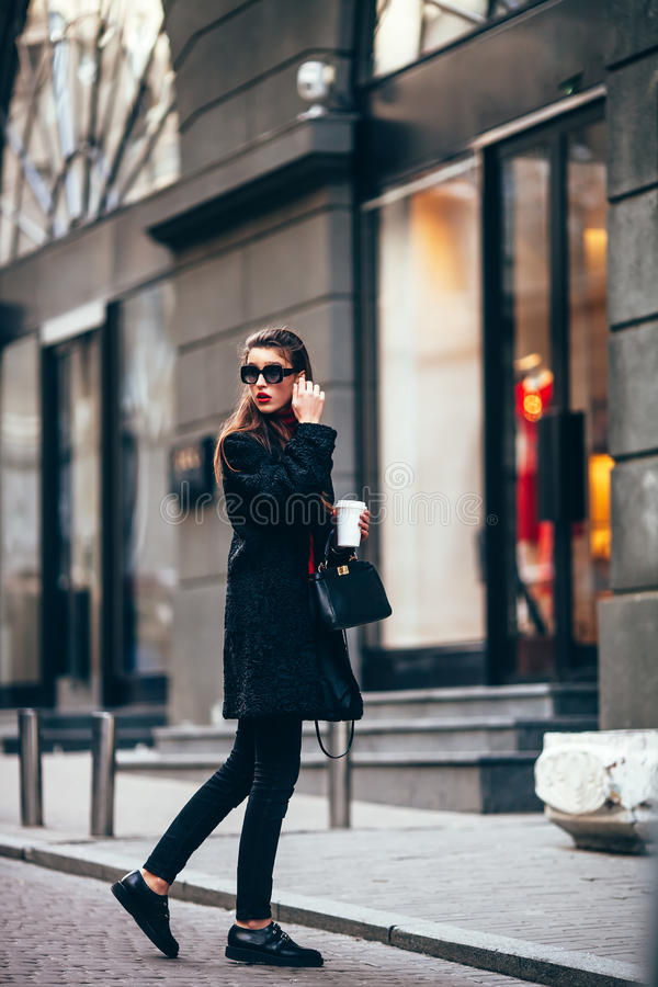 Menina à moda nova, passando por Windows Vidros elegantes vestindo e um revestimento preto Mantém o café fotos de stock royalty free
