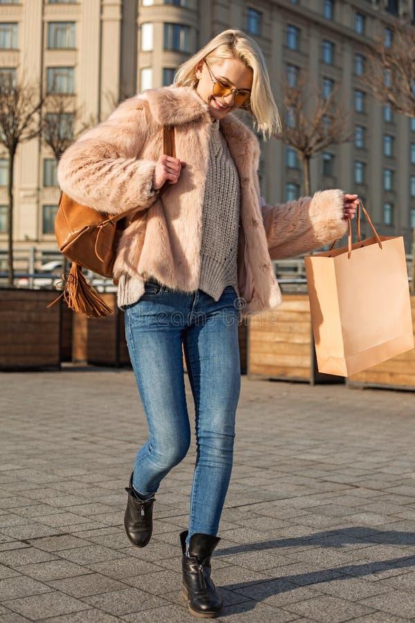 A menina à moda otimista está demonstrando a alegria ao levar o saco de compras foto de stock
