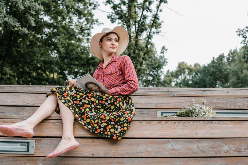 Menina à moda que lê um livro Uma mulher bonita com um chapéu que senta-se em escadas de uma árvore Um estudante l? um livro imagem de stock