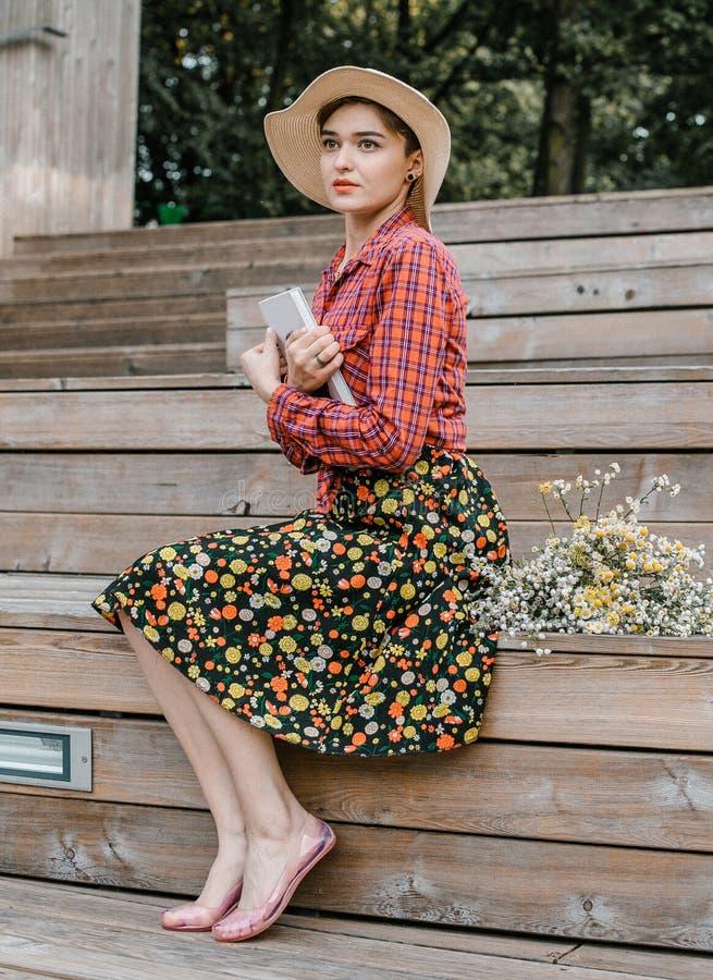 Menina à moda que lê um livro Uma mulher bonita com um chapéu que senta-se em escadas de uma árvore Um estudante l? um livro fotografia de stock royalty free