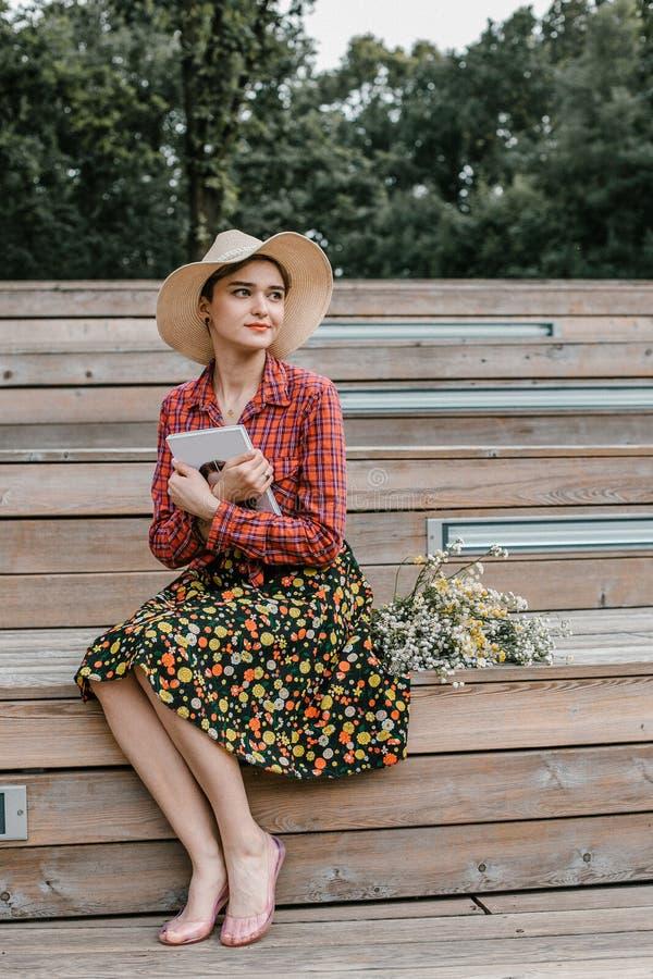 Menina à moda que lê um livro Uma mulher bonita com um chapéu que senta-se em escadas de uma árvore Um estudante l? um livro imagens de stock royalty free