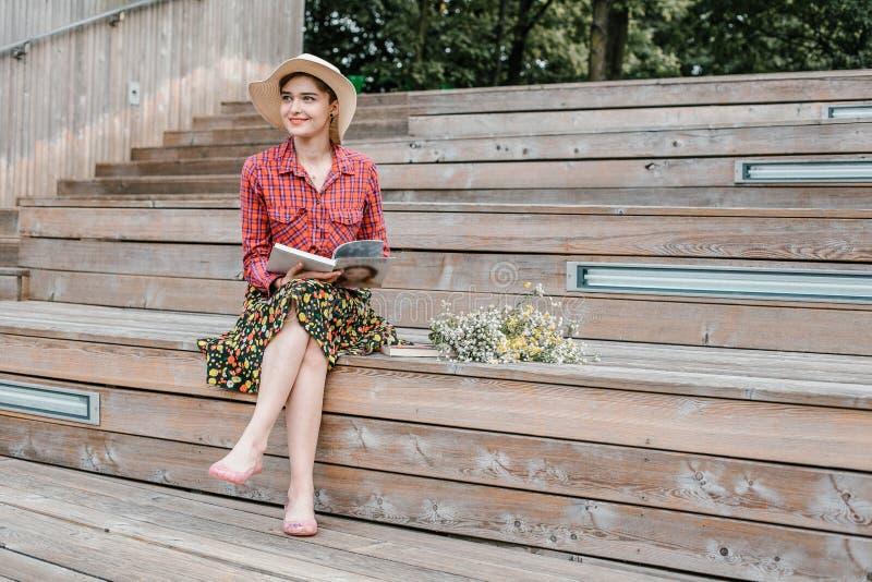 Menina à moda que lê um livro Uma mulher bonita com um chapéu que senta-se em escadas de uma árvore Um estudante l? um livro imagem de stock royalty free