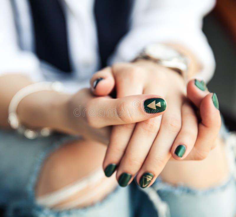 Menina à moda que senta-se em calças de brim rasgadas e no verniz para as unhas verde moderno, relógio, bracelete Forma, estilo d fotografia de stock