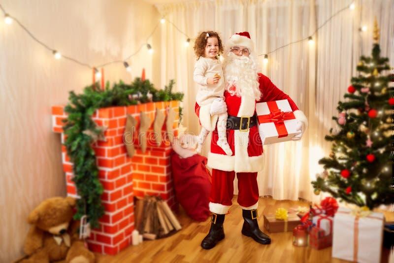 Menina às mãos de Santa Claus no Natal, um Ne feliz fotos de stock royalty free