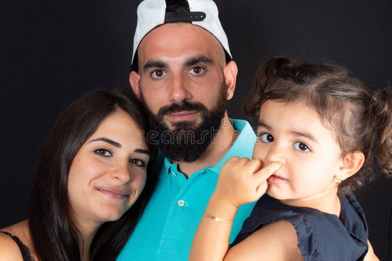 Menina árabe e seus pais no fundo preto imagem de stock royalty free