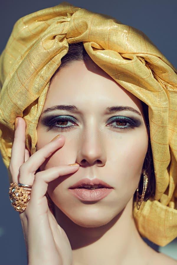 Menina árabe no turbante Joia do ouro Olhos fumarentos de turquesa da composição imagem de stock royalty free