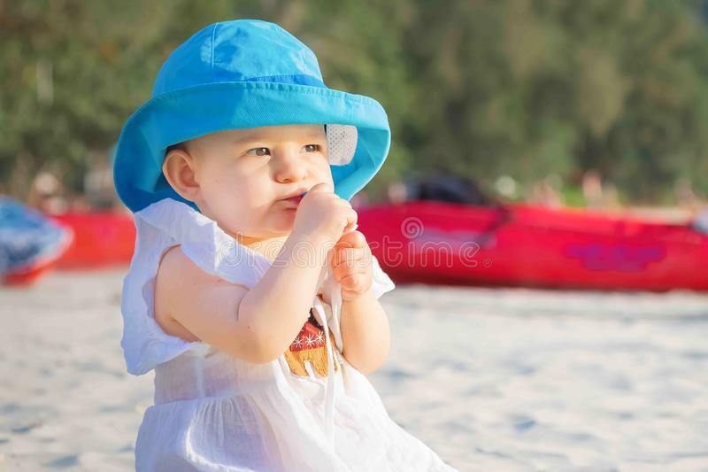 A menina ávida come algo na praia e não o quer compartilhar Está no vestido branco e no chapéu azul fotos de stock royalty free