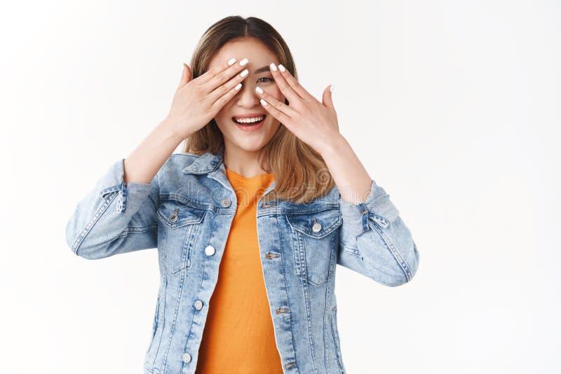 Menina ávida vê presente não consegue segurar antecipação tentadora olhar para a capa espiando pelos dedos alegres esperando imagem de stock