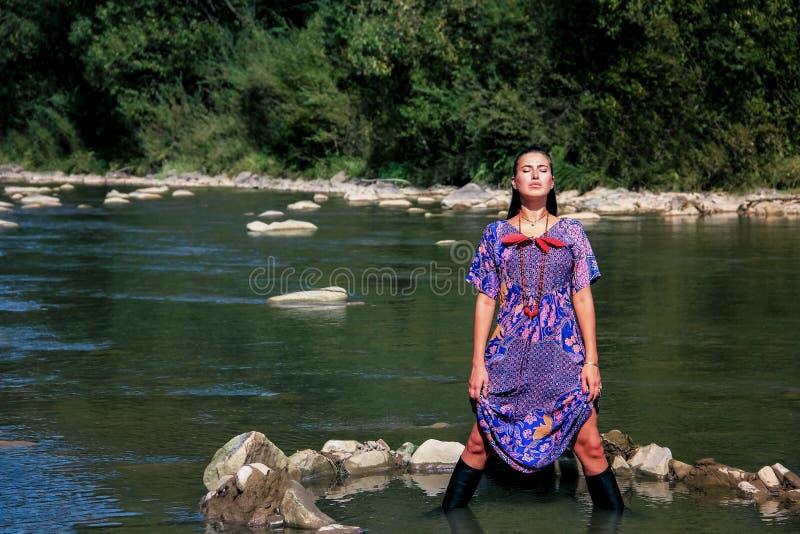 A menina é até o joelho em um rio da montanha fotos de stock royalty free