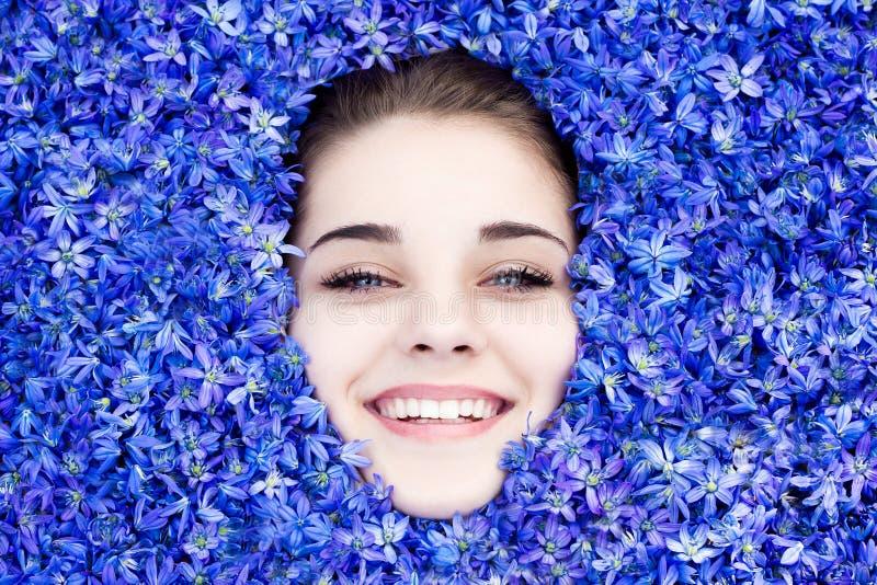 A menina é coberta com as flores azuis da mola, a menina olha para fora de debaixo das flores imagens de stock