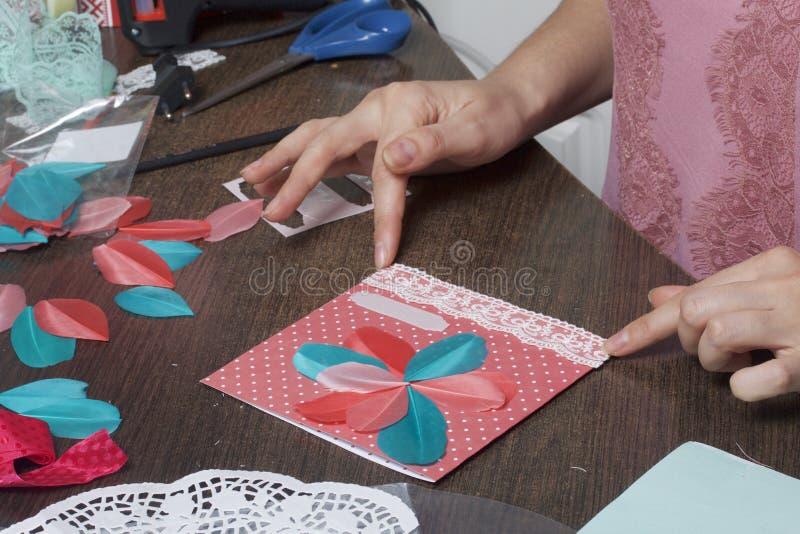 A menina é contratada em fazer cartões em casa Usando o papel, o laço, a trança e os outros materiais fotos de stock royalty free