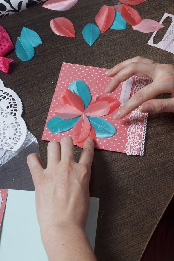 A menina é contratada em fazer cartões em casa Usando o papel, o laço, a trança e os outros materiais imagem de stock