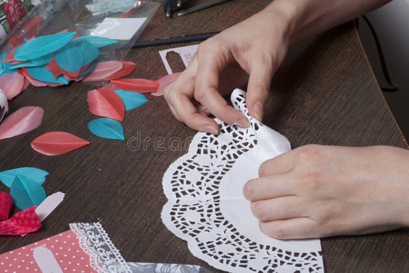 A menina é contratada em fazer cartões em casa Usando o papel, o laço, a trança e os outros materiais imagens de stock royalty free