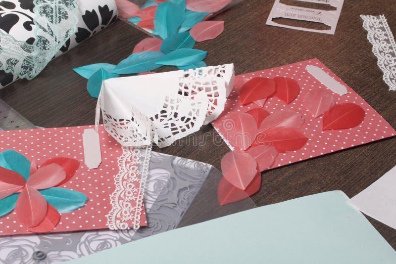 A menina é contratada em fazer cartões em casa Usando o papel, o laço, a trança e os outros materiais fotos de stock