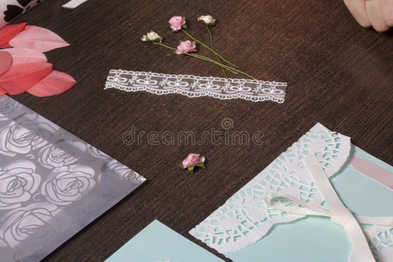 A menina é contratada em fazer cartões em casa Usando o papel, o laço, a trança e os outros materiais foto de stock