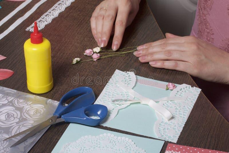 A menina é contratada em fazer cartões em casa Usando o papel, o laço, a trança e os outros materiais fotografia de stock royalty free
