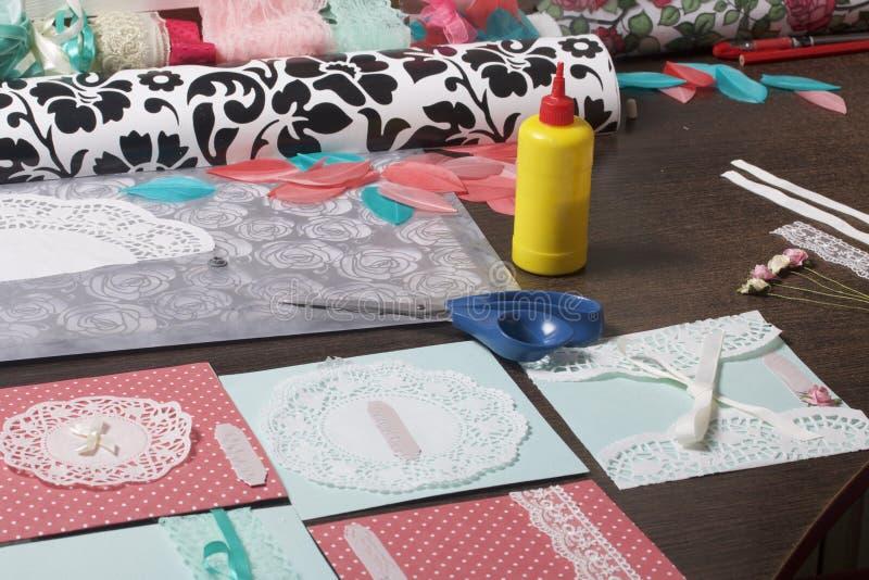 A menina é contratada em fazer cartões em casa Usando o papel, o laço, a trança e os outros materiais imagens de stock
