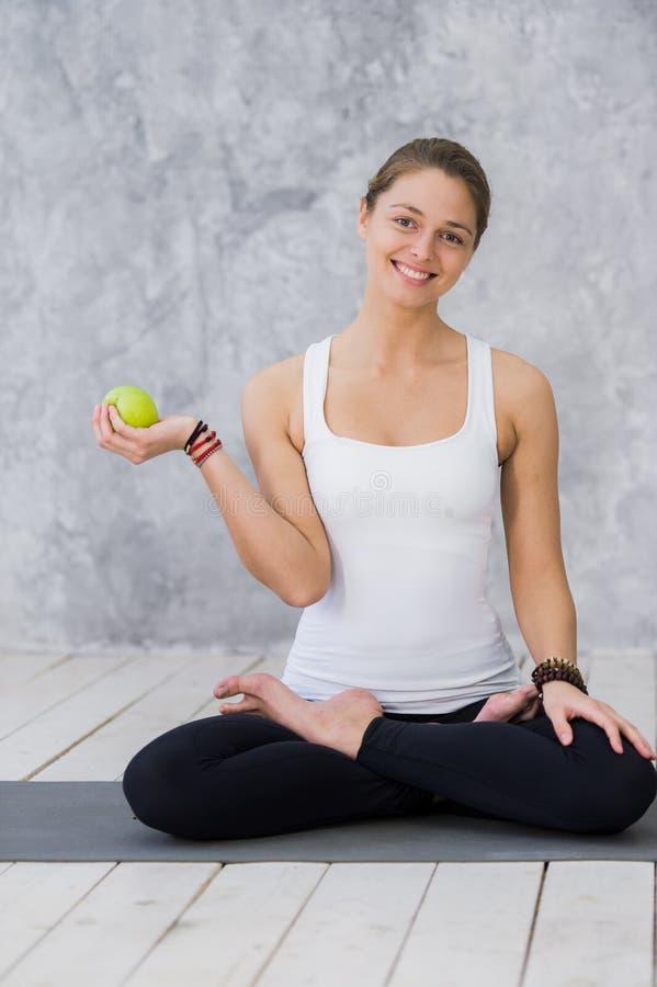A menina é contratada na ioga em um fundo branco, no conceito do estilo de vida saudável, em comer saudável e em esporte, maçãs fotografia de stock royalty free
