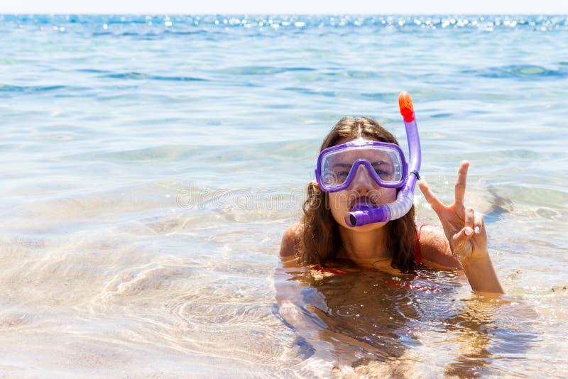 A menina é contratada no mergulho autônomo em um mar claro limpo a moça vestiu-se nos vidros e em um tubo para nadar imagens de stock