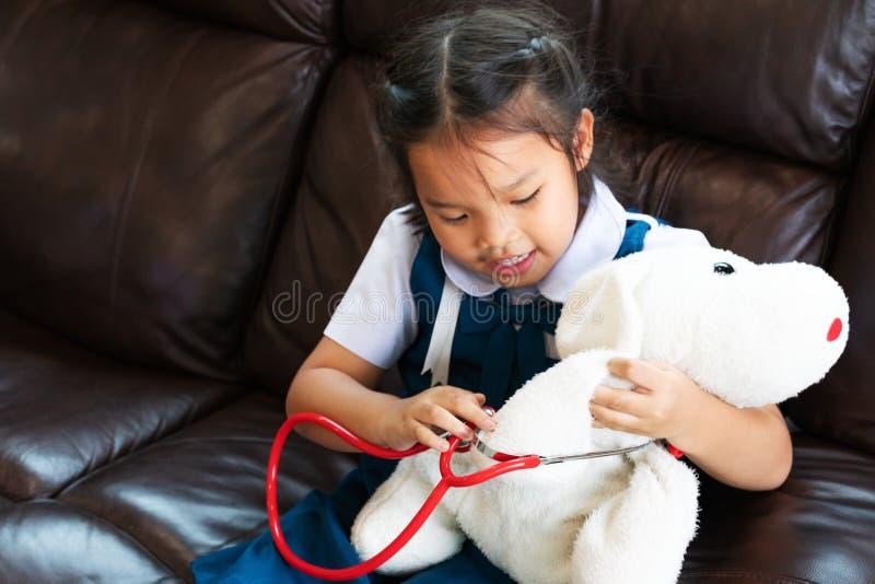 A menina é de sorriso e de jogo o doutor com estetoscópio Criança e conceito dos cuidados médicos imagem de stock royalty free