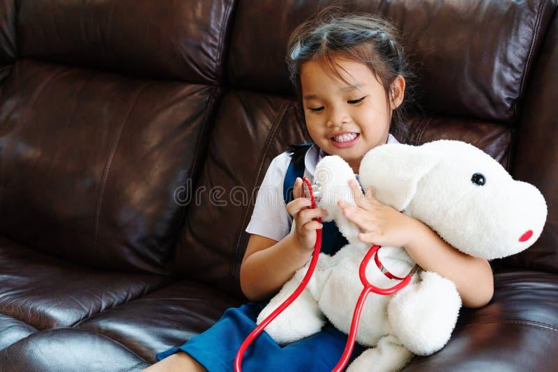 A menina é de sorriso e de jogo o doutor com estetoscópio Criança e conceito dos cuidados médicos foto de stock