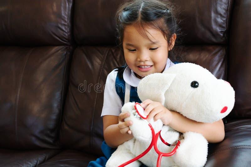 A menina é de sorriso e de jogo o doutor com estetoscópio Criança e conceito dos cuidados médicos fotografia de stock