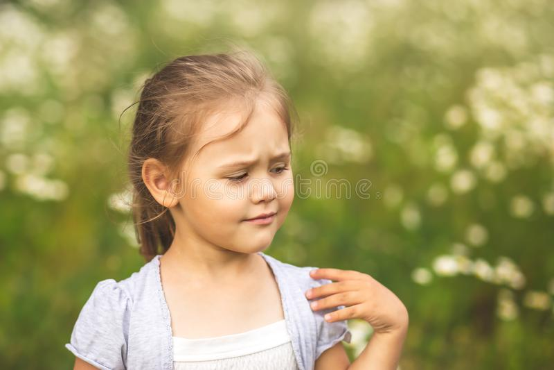 A menina é descontentada com algo, na natureza no verão imagem de stock