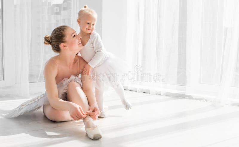 A menina é ensinada como amarrar sapatas do pointe do bailado fotos de stock royalty free