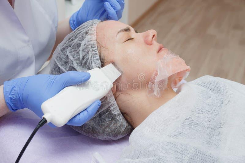 A menina é fornecida com um serviço de limpeza da pele do ultrassom no salão de beleza fotos de stock