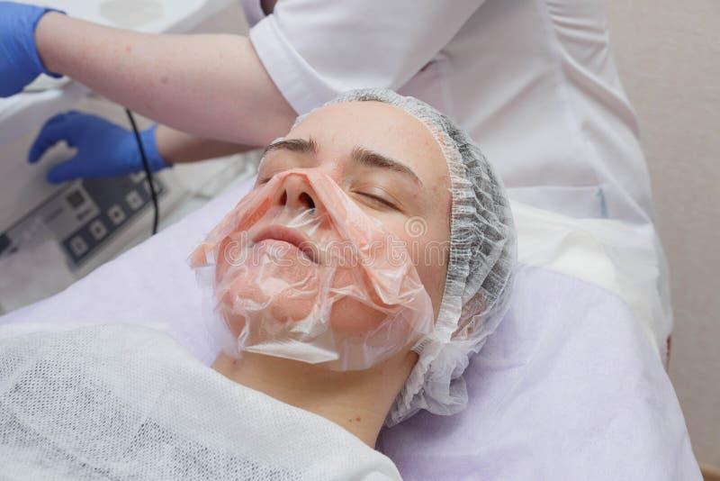 A menina é fornecida com um serviço de limpeza da pele do ultrassom no salão de beleza fotografia de stock