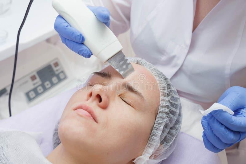A menina é fornecida com um serviço de limpeza da pele do ultrassom no salão de beleza fotos de stock royalty free