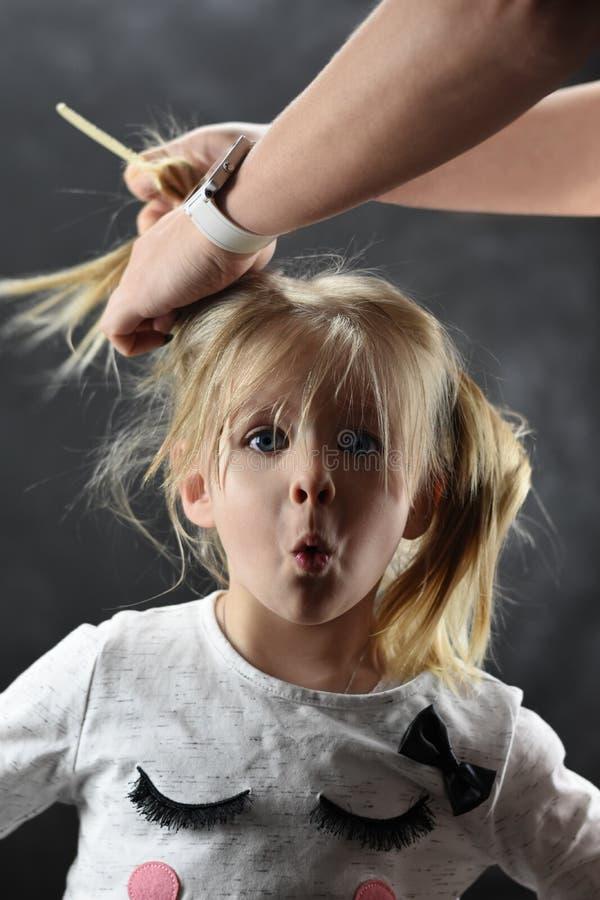 A menina é surpreendida muito ao pentear o cabelo com mãos fêmeas foto de stock