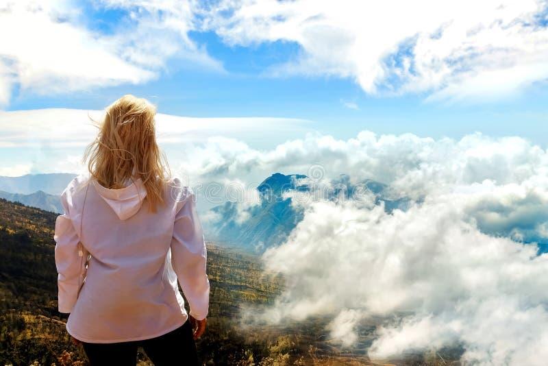 A menina é um viajante em um passeio na montanha da montanha Uma vista de cima nas montanhas e das nuvens Acima das nuvens Trekki imagem de stock