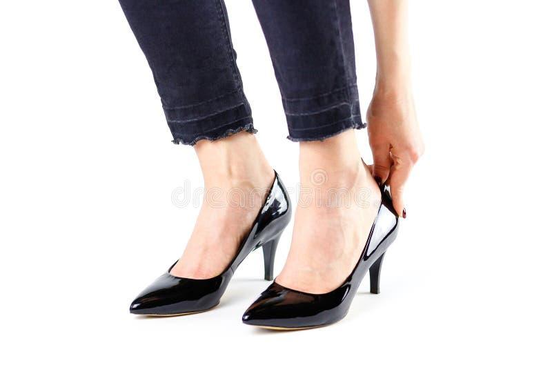 A menina é vestida em sapatas pretas Fim acima Em um whit fotografia de stock royalty free
