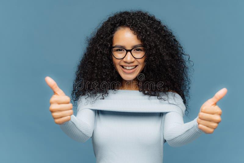 A menina étnica de vista agradável de suporte tem o cabelo escuro espesso, mostra os polegares acima, recomenda o serviço excelen fotografia de stock royalty free