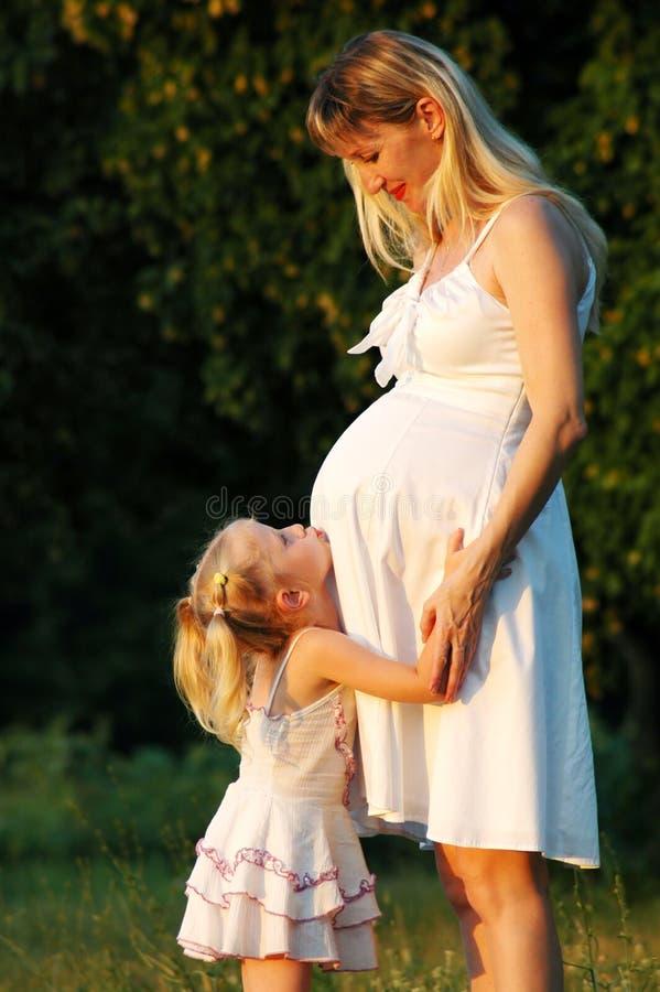 A menina abraça um mum grávido imagem de stock
