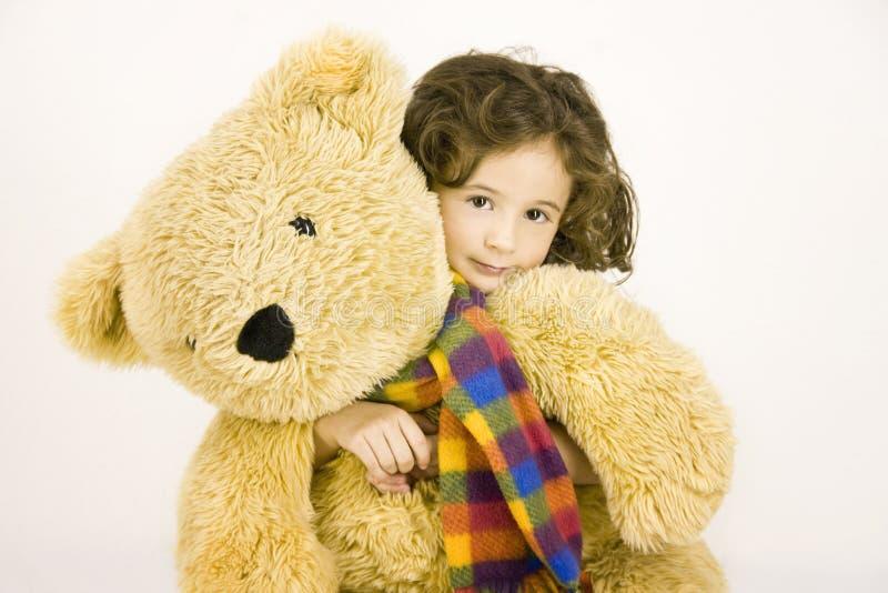 A menina abraça um urso de peluche grande imagem de stock royalty free
