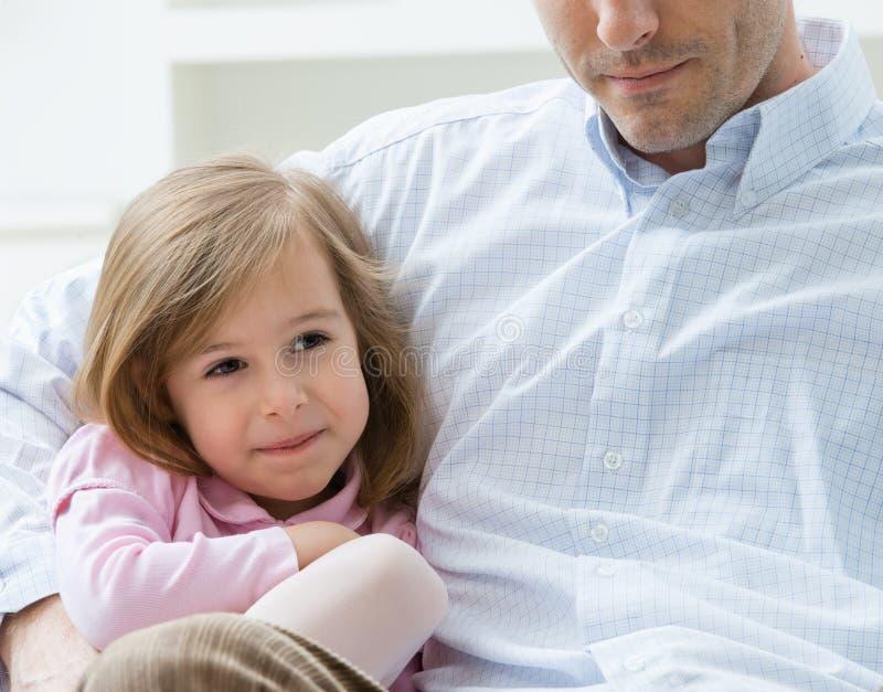 Menina abraçada pelo pai fotos de stock